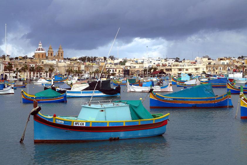 Fischerort Marsaxlokk. Die Fischerboote (luzzus) sind traditionell am Bug mit Augen verziert. Diese sollen die Fischer vor Gefahren schützen.