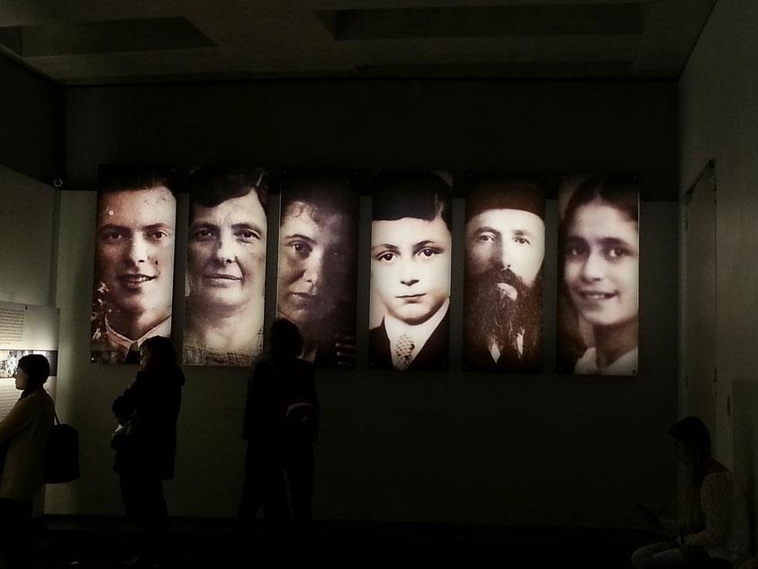 Ort der Information: Auftakt. Sechs großformatige Portraits stehen für die etwa sechs Millionen Opfer