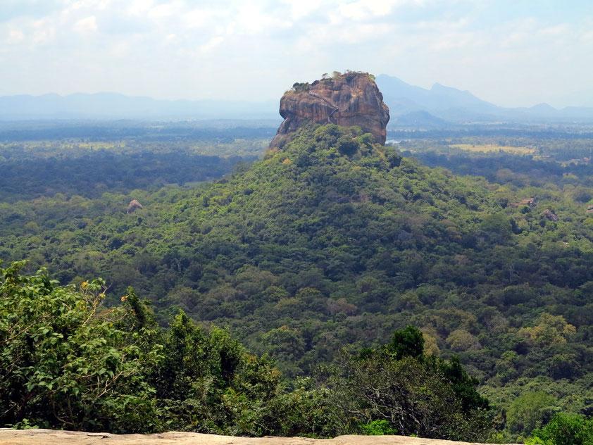 Sigiriya, ein vulkanischer Monolith (Stoßkuppe), auf dem sich die Ruinen einer historischen Felsenfestung befinden. Blick vom benachbarten Felsen Pidurangala
