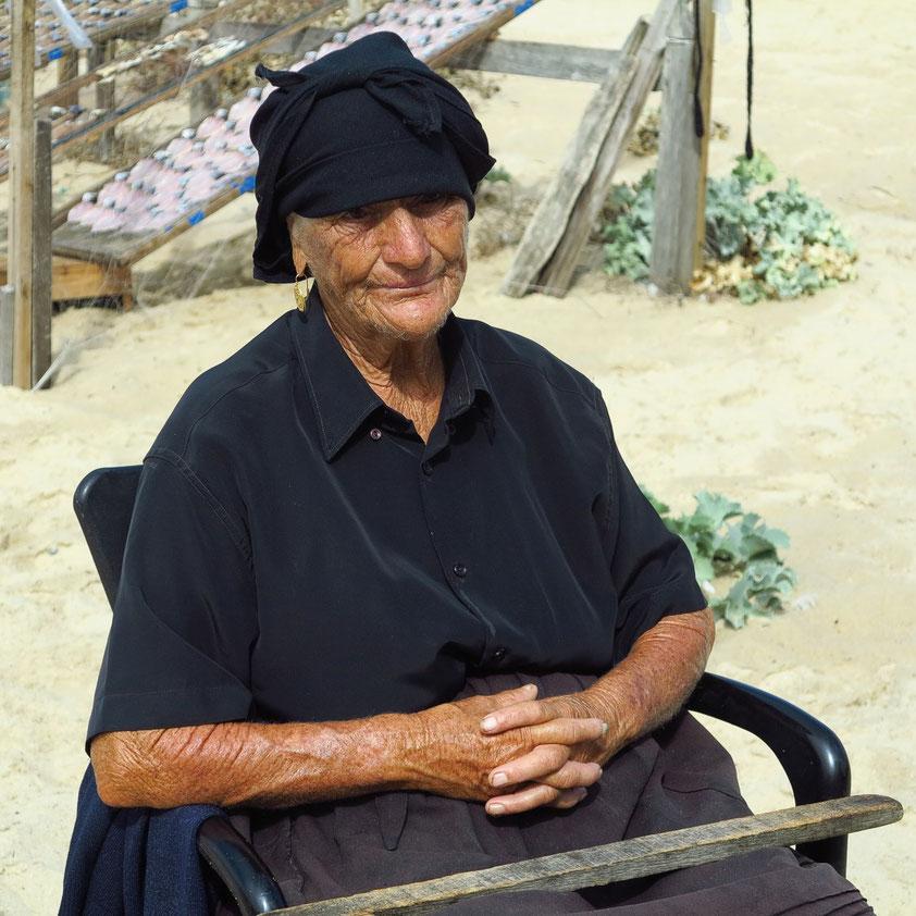 Die Fischerfrau am Strand von Nazaré erinnert an das alte Portugal.