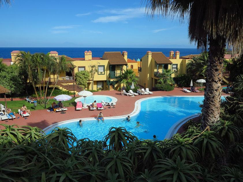 Apartamentos Oasis San Antonio, Poollandschaft mit Blick nach Osten zum Atlantik, am Horizont der Pico de Teide auf Teneriffa (120 km Luftlinie)