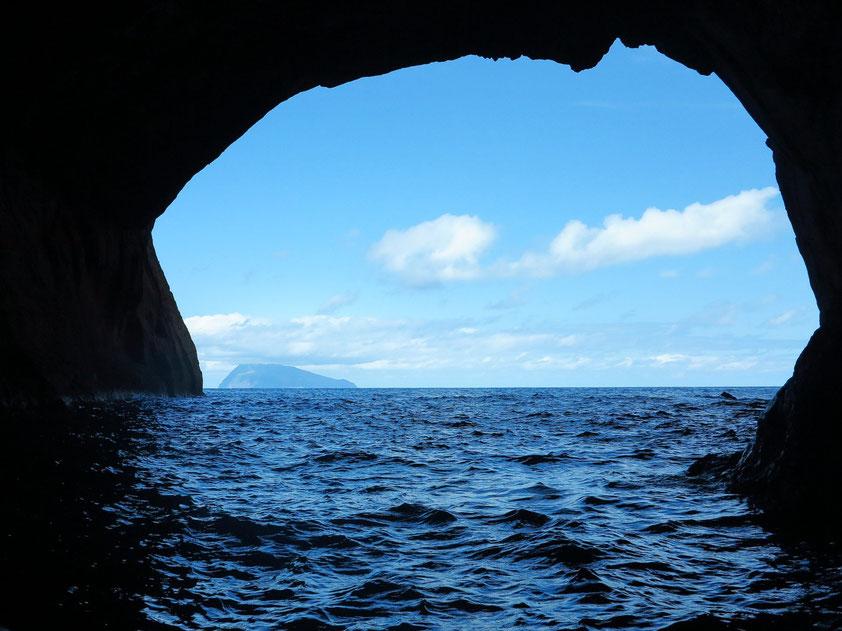 Flores, Blick aus einem Höhlentor, am Horizont die Insel Corvo