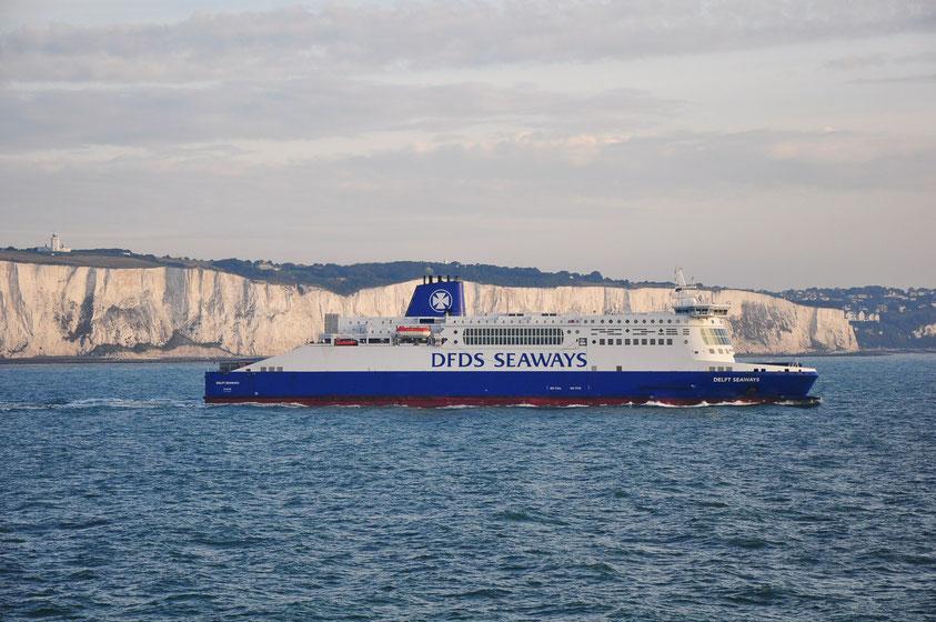 Kreidefelsen von Dover. Links der South-Foreland-Leuchtturm über den Felsen von Dover. Ein Fährschiff hat den Hafen von Dover mit dem Ziel Festland verlassen.