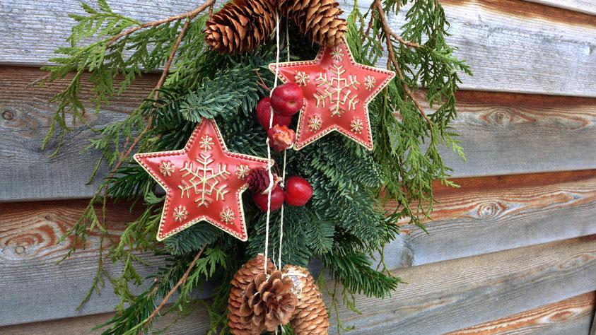 Weihnachtliche Türdekoration aus Tannengrün und Zieräpfeln