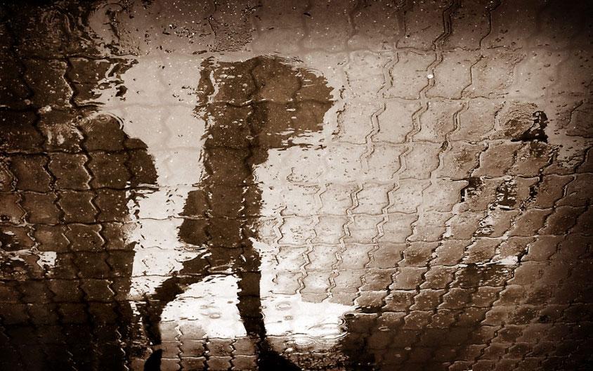 Reflecties van wandelaar met paraplu in regenplas