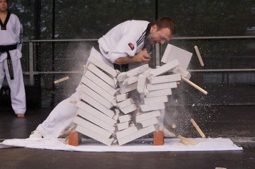 Taekwondo-Meister zerschlägt Betonplatten mit seinem Ellenbogen für eine Vorführung auf einer Bühne.