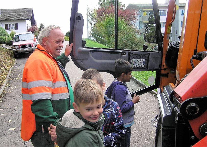 Schulkinder im Gespräch mit einem Müllabfuhrmitarbeiter am Müllauto