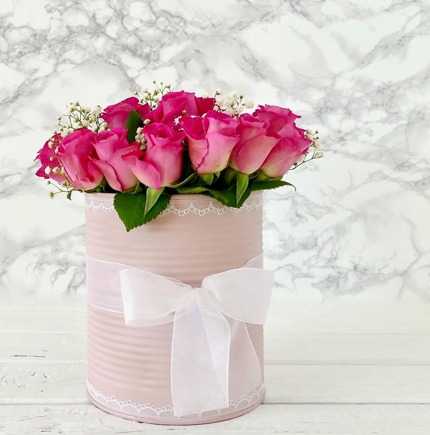 Pinkfarbige Rosen in rosa Dose mit weisser Schleife