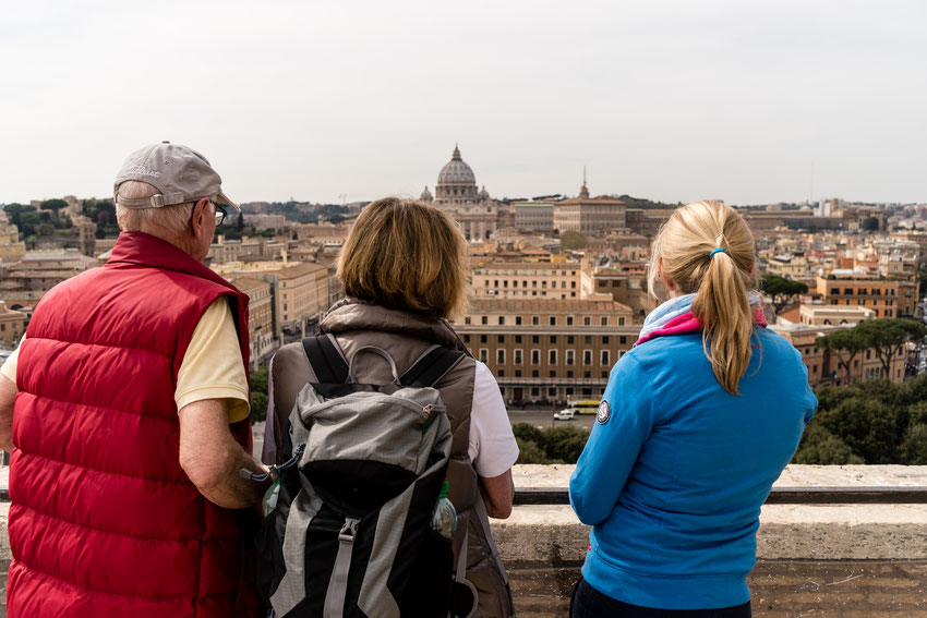 Drei Personen schauen auf die St. Peter's Basilika in Rom