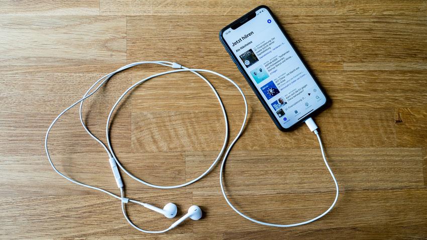 Handy mit Kopfhörer und Podcasts auf Display