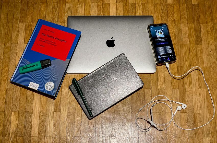 Laptop, Buch, Handy und Notizbuch auf dem Boden