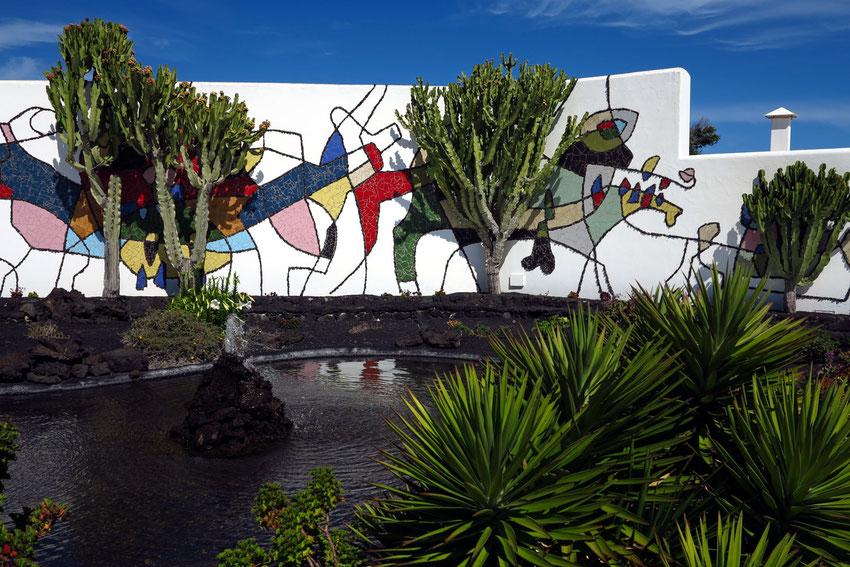 Garten mit Wandgemälde von 1992. Für den Umriss ist vulkanisches Gestein und für die Innenflächen sind Fliesen verwendet worden.
