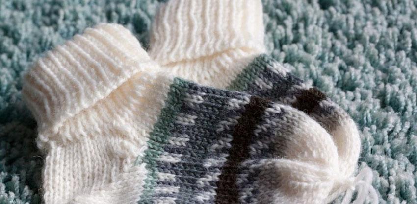 Auf einem grauen Fellteppich liegt ein Paar selbstgestrickter Socken in den Farben weiß, grau und grün.