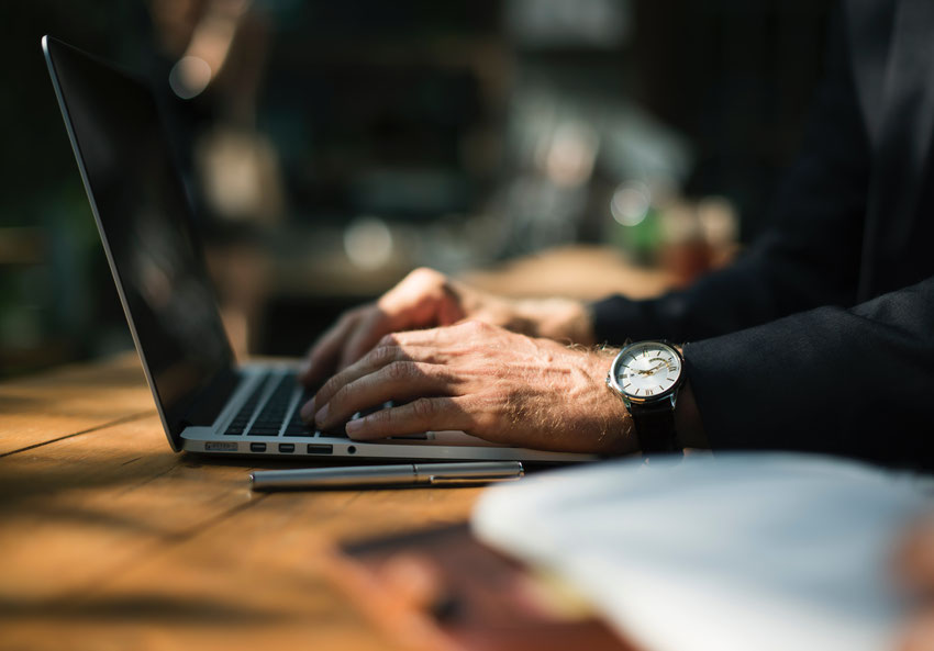 Laptop mit schreibenden älteren Händen