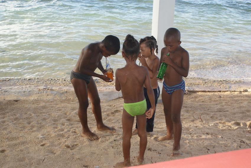 """Am Strand beim Restaurant """"Coral Reef Bar & Restaurant"""" haben die Kinder jede Menge Spaß im Wasser und beim Soft-Drink-Wetttrinken."""