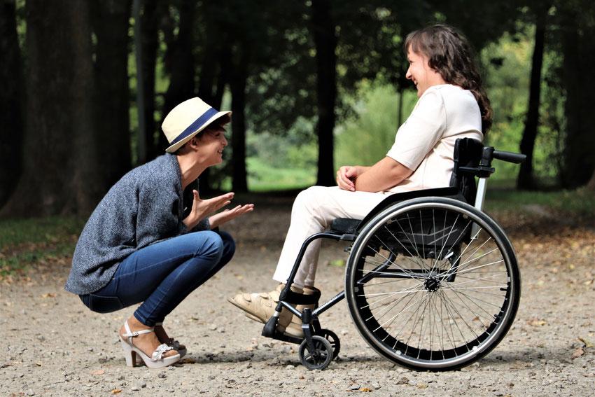 Ein Junge im Rollstuhl. Vor ihm ein grünes Kuscheltier. © AdobeStock