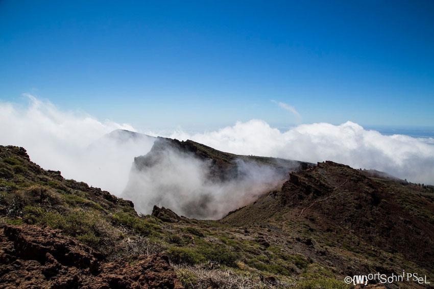 Wolken wandern am Rand des Roque de los Muchachos entlang