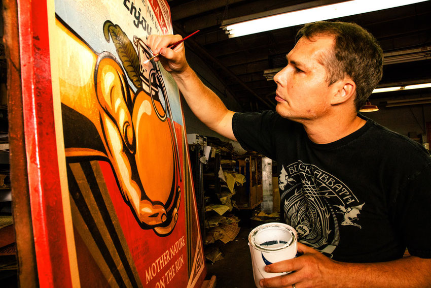 shepard fairey working on street art painting