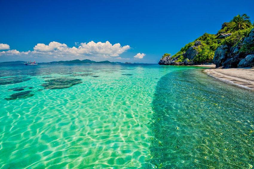 Ilgais, baltais Tailando paplūdimiais ritasi skaidrios bangų juostos