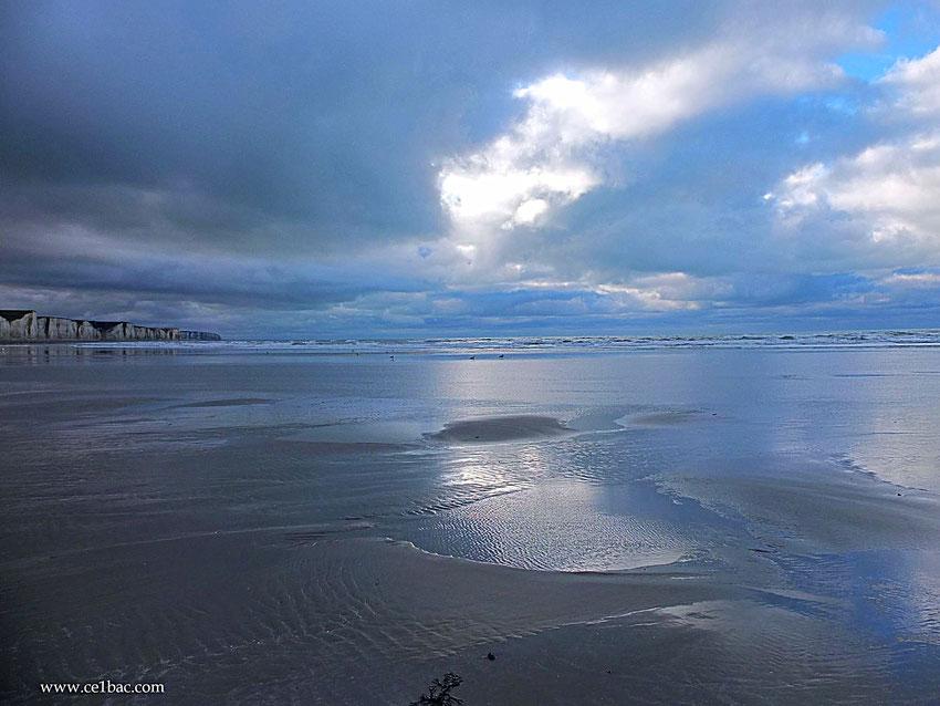 nuages sur le sable mouillé