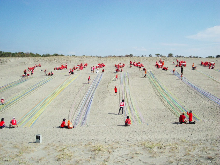 Making of Land art in sand dunes. Japanese educational art project 2012