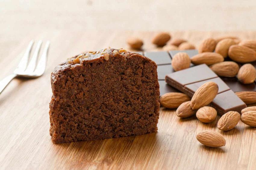 Schokoladen Kuchen aus dem Glas herausgelöst mit den wichtigsten Zutaten: Schokolade und Mandeln