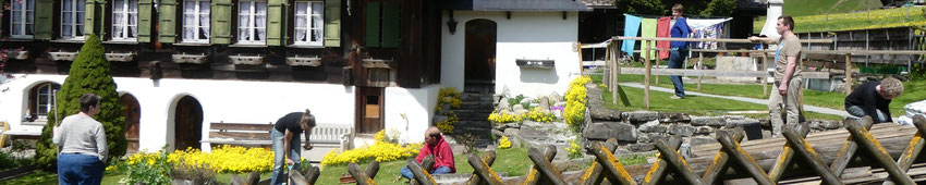 Behinderte erledigen mit einer Betreuerin Gartenarbeiten.