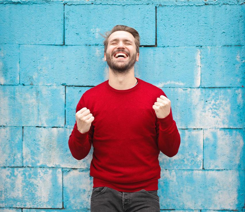 Mann glücklich vor blauer Hauswand