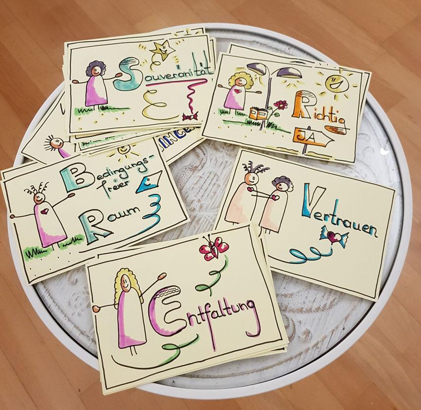 Wertekarten auf dem Tischen zeigen Entfaltung, Vertrauen, Souveränität und bedingungsfreie Räume