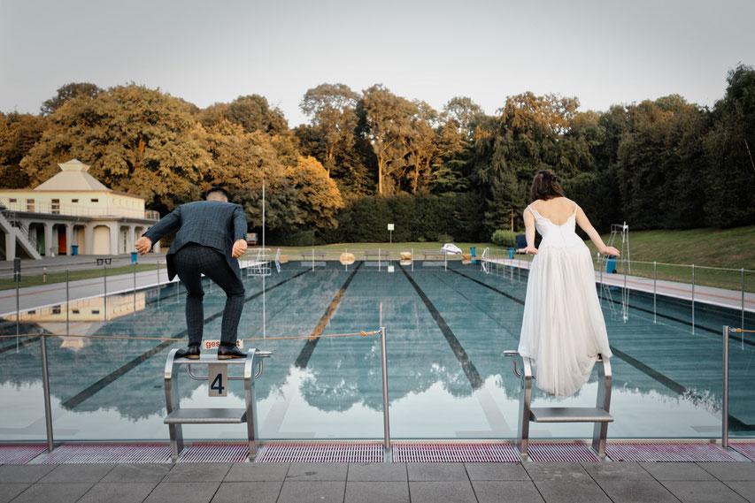 Ein Brautpaar tut so, als ob es gleich in ein Freibad springt.