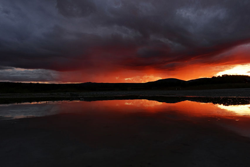 Es war so kitschig! Regenvorhänge wurden orangerot angestrahlt. Im Vordergrund ist kein See, sondern ein kleine Pfütze.
