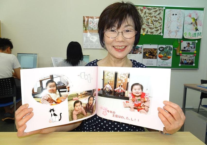 自ら作ったフォトブックを手に微笑む生徒さん