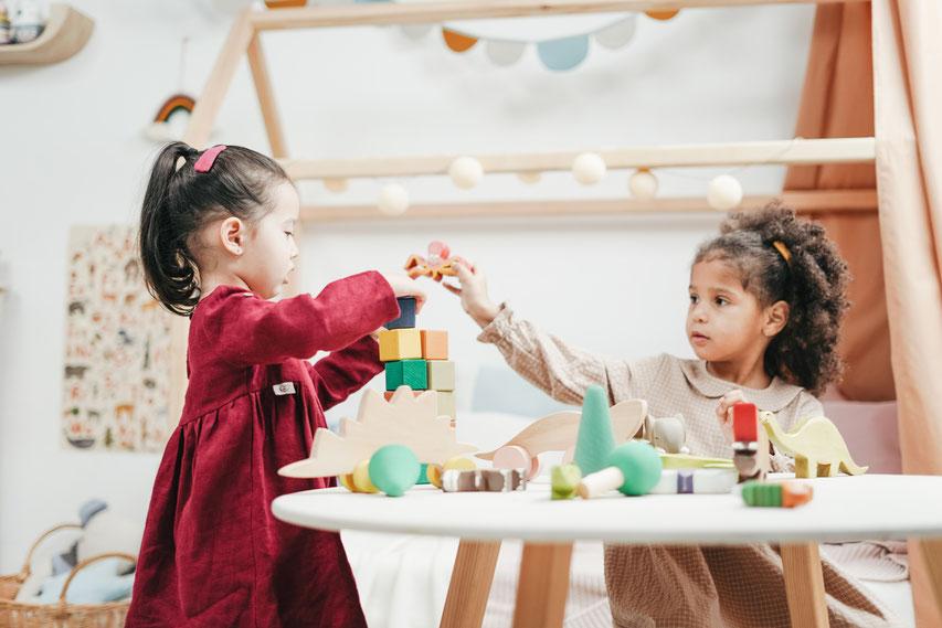 Kinder im Kindergarten spielen mit Bauklötzen, haben Spaß, sich ausgelassen und entspannt, haben keine Verlustängste