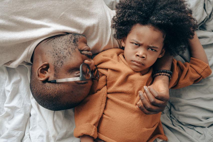 Vater und Sohn liegen auf dem Bett und ruhen sich aus nach dem Kindergarten, Das  Kind istb wütend. Der Vater begleitet ihn liebevoll und bedürfnisorientiert