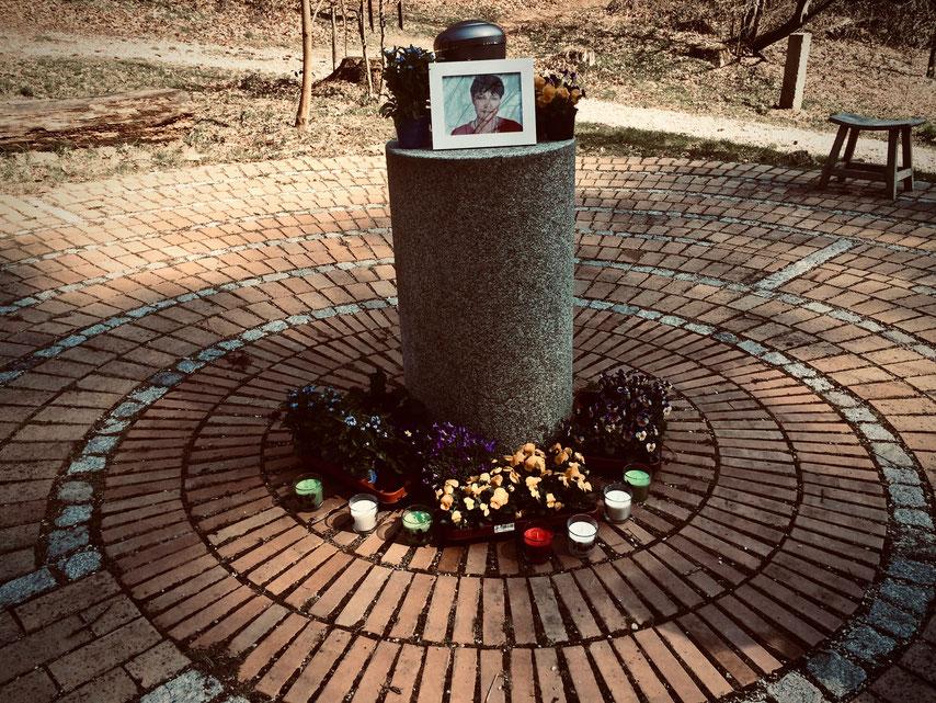 Trauerfeier: Gedenkstein mit Blüten im Bach