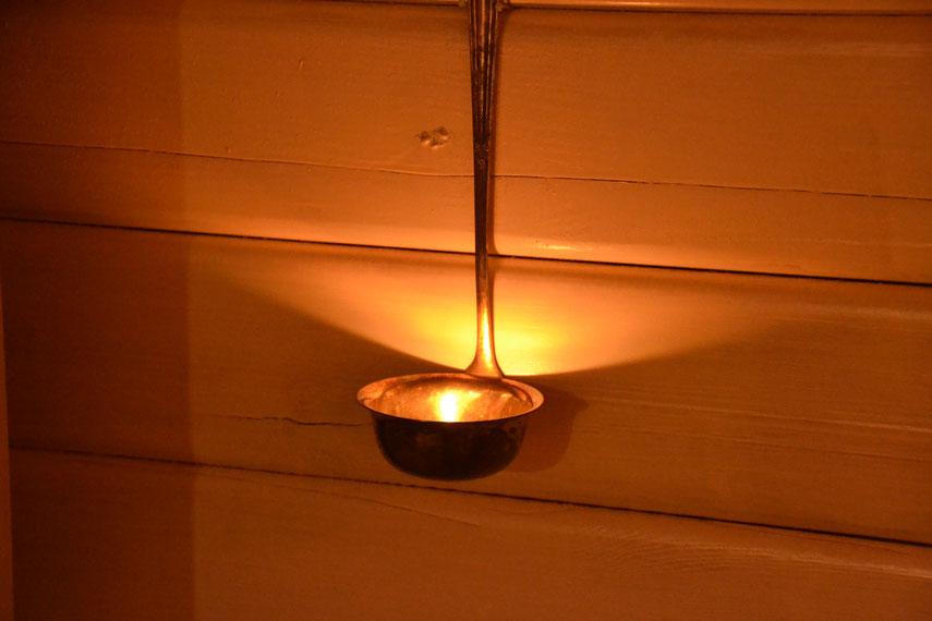 Eine große alte Suppenkelle wird gerade gebogen und  zwischen zwei Nägeln an die Bohlen gehängt zur festlichen Beleuchtung