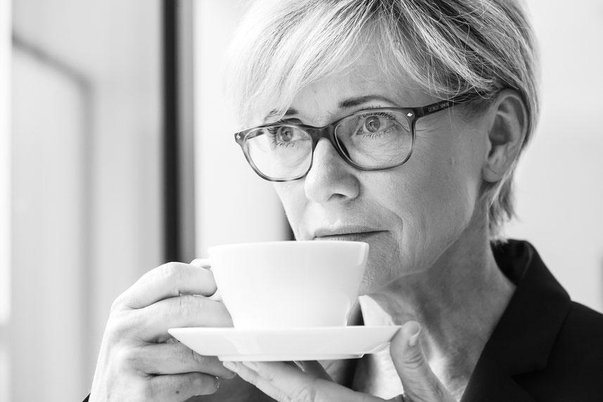 Heike Regina Nirschl überlegend mit Kaffeetasse