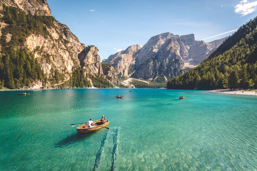 See mit Booten und Bergen im Hintergrund