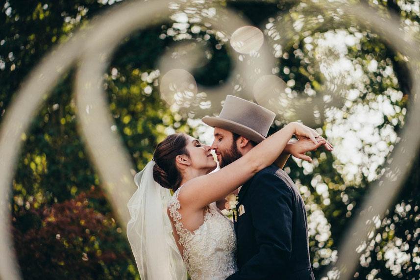 Brautpaar küsst sich im Garten der Hochzeitslocation Gutsgasthof Stangl bei München