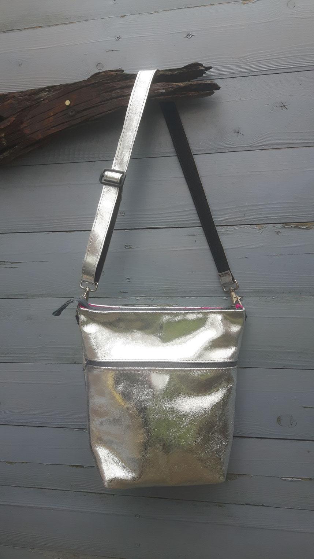 Silver lining. Leren tas met ritssluiting, knalroze voering en handig extra ritsvak. Zilver gespoten leer.
