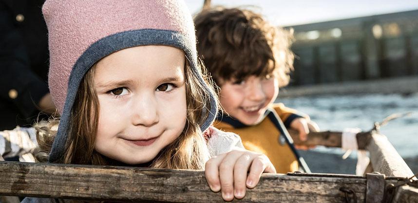 mädchen mit rosa walkmütze und junge in curryfarbener walkjacke aus merinowolle und biobaumwolle für kinder, nachhaltig produziert
