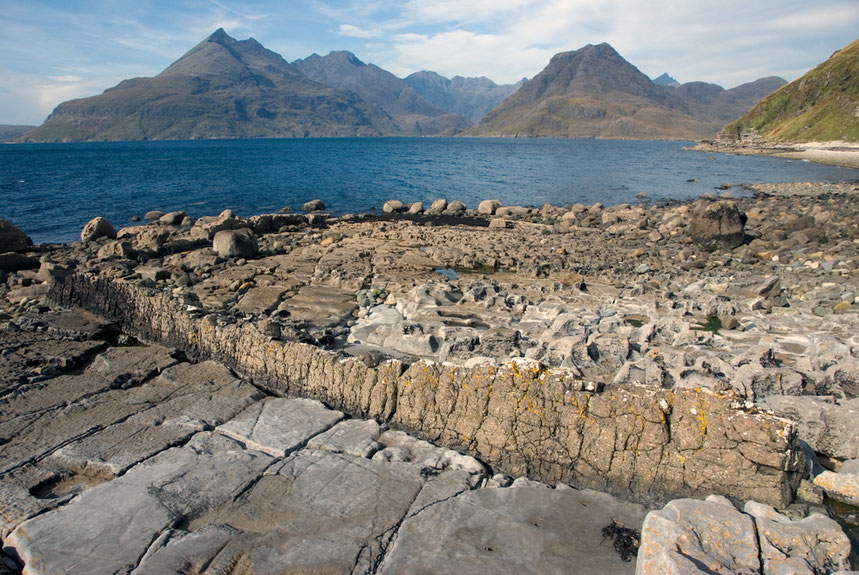 The Cuillin massif on the Isle of Skye from the north of Elgol with a fine dyke in the foreground in the Jurassic limestoones and mudstones in the foreground.