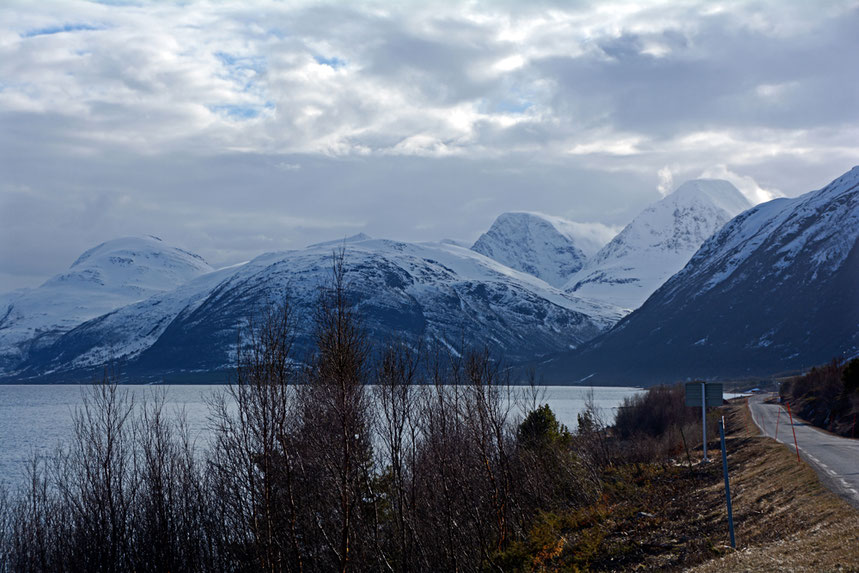 The road down the east side of the Storfjorden with high Lyngen peaks and the steep-sided valley side near Pollfjellet where a rockfall created a tsunami in 1810 that claimed 13 lives.  There is now a grim 3.2km tunnel under Pollfjellet.