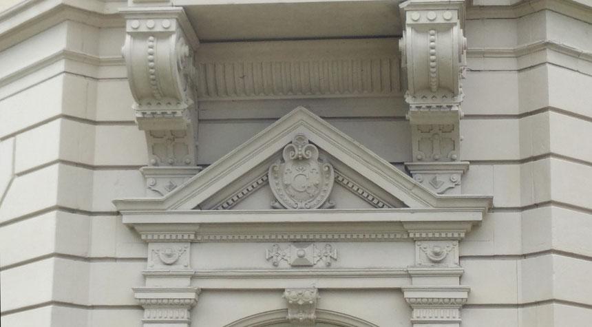 """Hotel Grunewald, Initial """"G"""" über dem ehemaligen Geschäfts-Eingang, der kurz nach der Erstellung der Villa in ein Fenster umgewandelt wurde.  Hinter diesem Fenster ließ sich Elvis etwa 70 Jahre später auf einem grünen Sofa fotografieren, Foto: van Ooyen"""