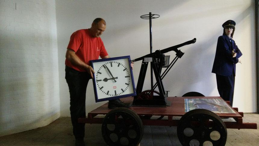 Stefan John, Vorsitzender der Eisenbahnfreunde Wetterau e.V., nimmt die Uhr aus der Bahnhofshalle des Bad Nauheimer Bahnhofs entgegen