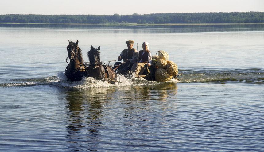 Žemaitukai brenda per ežerą su vežimu