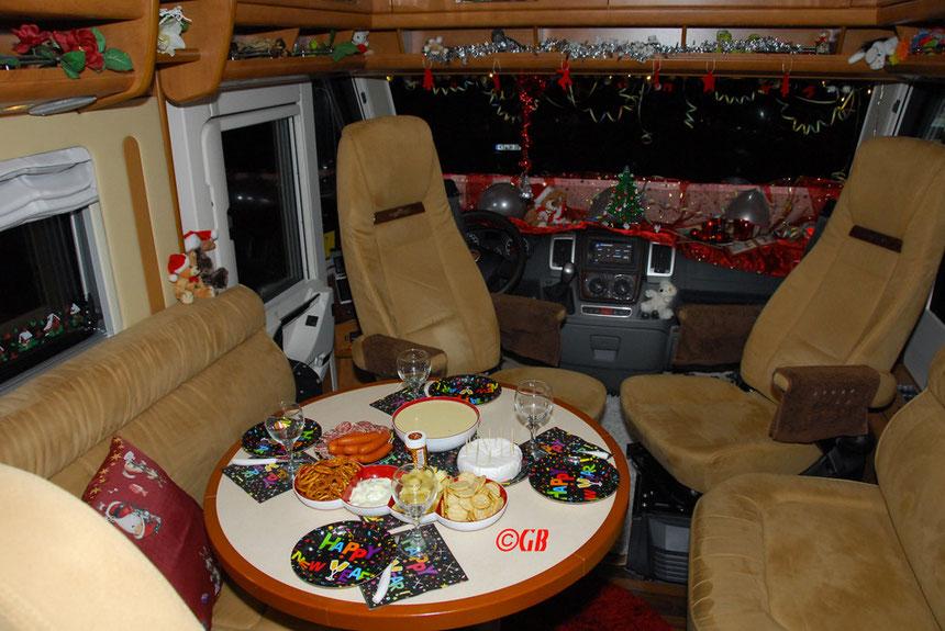 Silvesterfeier im Carthago Chic e-Line 51QB (La Casita) in Bad Königshofen. Wohnmobil mit gedecktem Tisch, Weihnachtsdekoration und die Spezialität des Hauses Kochkäse.