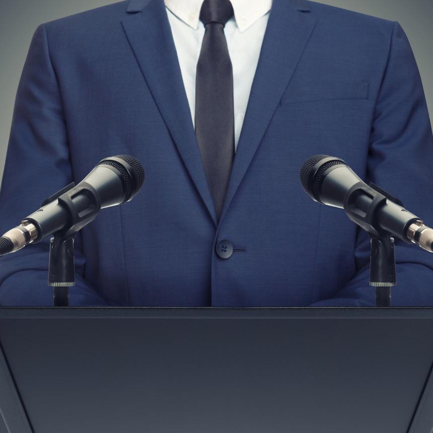 Mann in blauem Anzug (ohne Kopf) vor Mikrofonen an Rednerpult. Soll einen Politiker verkörpern
