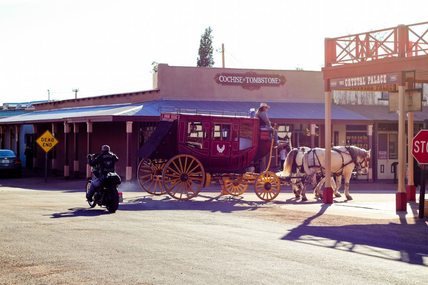 crossroad in tombstone arizona a sign shows dead end for a biker heading towards it, on other path of the road a old school carriage passes by with horses pulling it. Time crossroads because two distinct methodes of transportation cross eachover