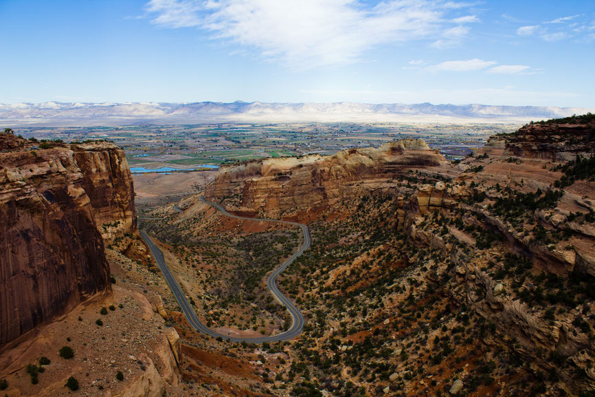 A canyon road following the countours of the mountain in grand junction colorado which we can see in the distance